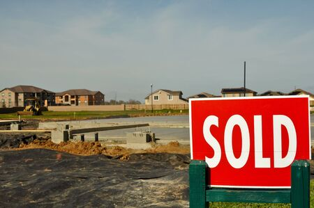 Red and white Sold Sign with new homes in the background Stock Photo