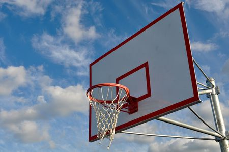 Outdoor Basketball Hoop Close Up with Clouds and Blue Sky photo