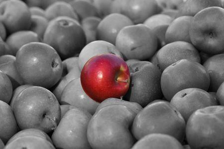 adentro y afuera: Destaque entre la multitud de Red Apple en medio del grupo de promedio de blanco y negro  Foto de archivo
