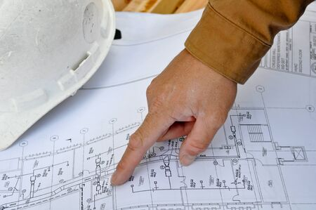 architect drawing: Human Hand Pointing at Construction Plans Stock Photo