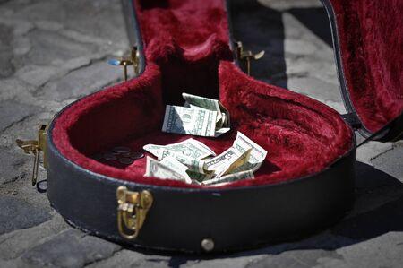 guitar case: Caso de guitarra de acera con dinero pidiendo donaciones o consejos