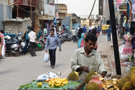 BANGALORE, IN - JUNE 30: Vendor sells coconuts on an unnamed street in Bangalore, IN June 30, 2011 in Bangalore, India. 42% of India falls below the international poverty line of $1.25 a day.