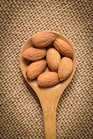 Almonds in a Wodden Spoon on a Burlap Background photo