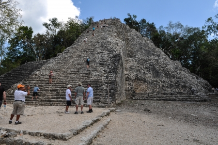 COBA,MEXICO - FEBRUARY 19: Group of tourists climb down the steep Nohoch Mul pyramid in Coba, Mexico on February 19, 2011. The main attraction to Coba is that you can climb the pyramid.