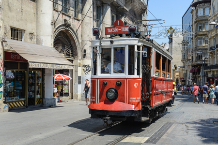 gained: ISTANBUL, TURKEY - JULY 09: Old-fashioned red tram at the street Istanbul on July 09, 2014. Nostalgic tram is the heritage tramway system. It was re-established in 1990 and gained much popularity. Editorial