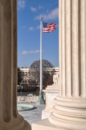 supreme court: Flag flying between two pillars of the Supreme Court of the United States