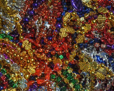 Background made up of mulit-colored including gold, purple, blue, green and pink mardi gras beads photo