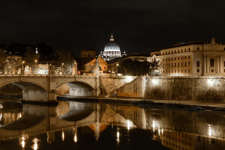 consecrated: ROME, ITALY -OCTOBER 18, 2014: Monumental St. Peters Basilica over Tiber at night in Rome, Italy. St. Peters Basilica is papal late renaissance basilica consecrated in 1626.
