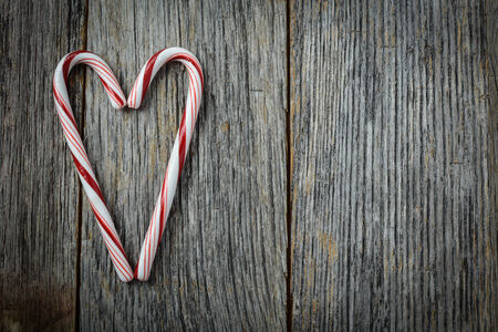 Heart shaped Candy Canes on a Rustic wooden Background photo