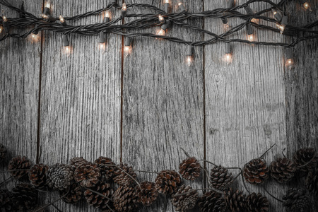 Christmas Lights and Pine cones on Rustic Wood Background photo