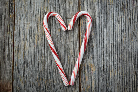 Heart shaped Candy Canes on a Rustic wooden Background Stock Photo