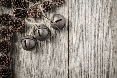 Pine cones and Rustic Bells on an Old Wood Background photo