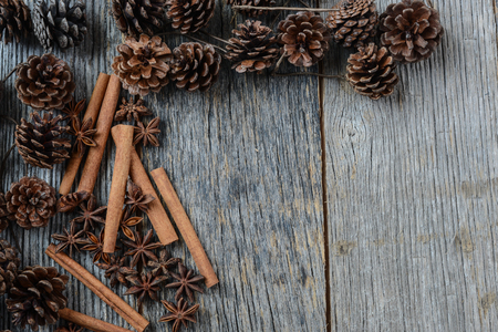 pomme de pin: Bâtons de cannelle, l'anis étoilé et pommes de pin rustique sur fond de bois