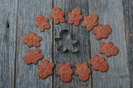 wood cutter: Gingerbread Cookie and Cutter on Wood Background