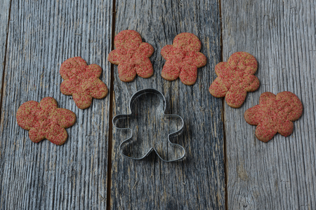 Gingerbread Cookie and Cutter on Wood Background photo