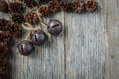 door bell: Pine cones and Rustic Bells on an Old Wood Background