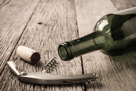 Green Wine Bottle and Cork with Red Wine and corkscrew photo