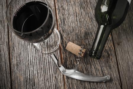 corcho: Botella de vino verde y del corcho con el vino rojo y sacacorchos