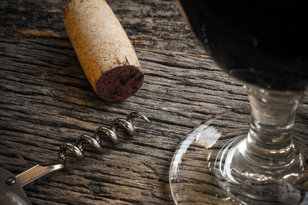 vins: Wine Glass with Cork and Corkscrew on Rustic Wood Table