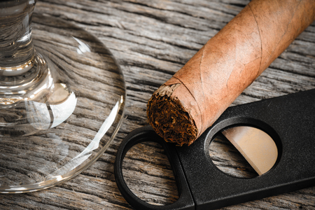 cigar smoke: Cigar and Cutter with Glass of Brandy or Whiskey on Wooden Background