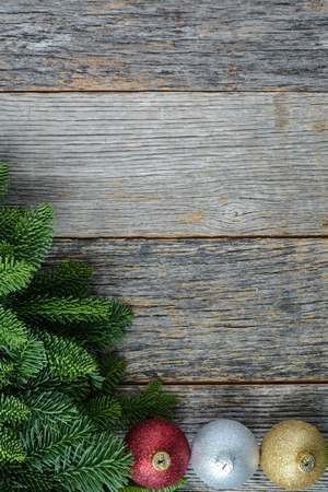 Christmas Pine Needle and Ornaments on a Rustic Wood Background photo