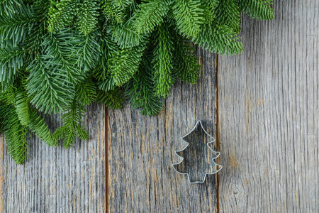 Tree branch on rustic wooden background  with cookie cutter ornament photo
