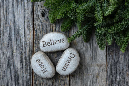 hope: Hope, Dream, Believe in Christmas with Pine Needles on Rustic Wood Background Stock Photo