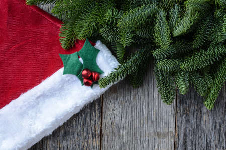 Pine Tree Branches and Santa Hat on Rustic Wood Background photo