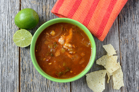 sopa: Tortilla Soup with Chips and fresh lime on Rustic Wood Background