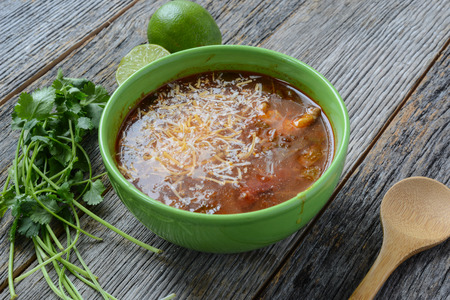 Tortilla Soup with Cheese, Lime, Cilantro and Wooden Spoon on Rustic Wood Background photo