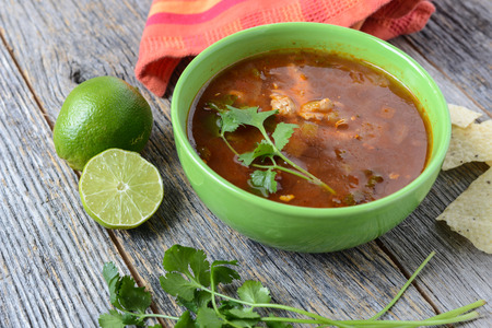 Tortilla Soup with Chips, fresh lime and cilantro on Rustic Wood Background photo