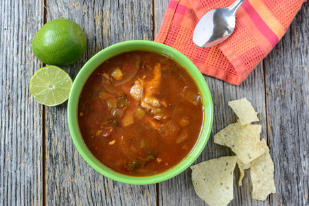 Tortilla Soup with Chips, fresh lime and spoon on Rustic Wood Background photo