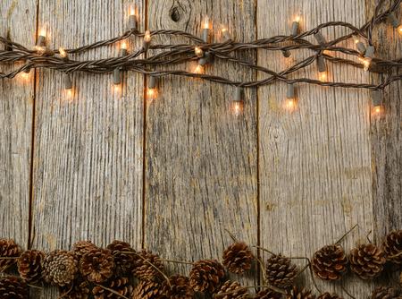 소박한 나무 배경에 크리스마스 조명과 소나무 콘 스톡 콘텐츠