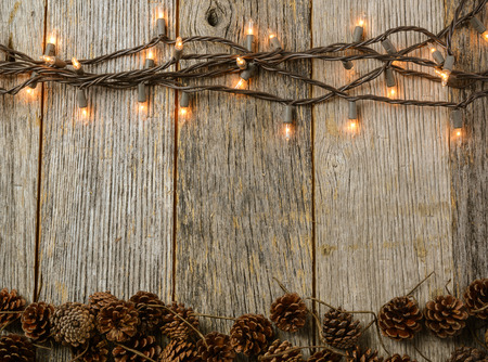 moody background: Christmas Lights and Pine cones on Rustic Wood Background