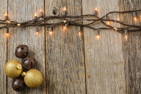 natural  moody: Christmas Tree Lights with Rustic Wood Background and Gold Ornaments and Bells