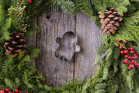 wood cutter: Christmas Wreath with Gingerman Cookie in the Middle of Wood Background