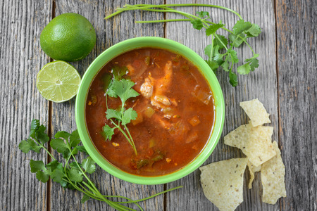 close up food: Tortilla Soup with Chips, fresh lime and cilantro on Rustic Wood Background