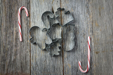 Holiday Cookie Cutters and Candy Cane on Rustic Wood Background photo
