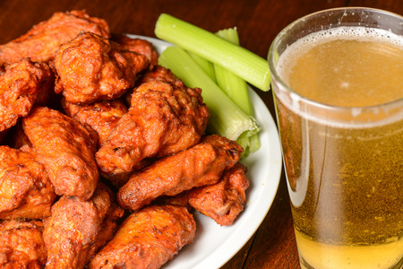 Buffalo Wings with Celery Sticks and Beer Imagens