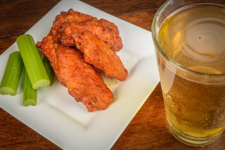 Chicken Buffalo Wings with Celery Sticks and Beer photo