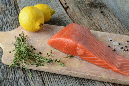 Salmon on a Cutting Board with Lemon, Salt and Pepper photo