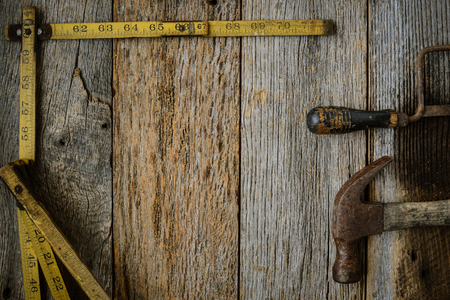 Measuring Tape Hammer and Saw on Rustic Old Wood Background photo
