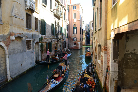 VENICE, ITALY - OCTOBER 22: Gondolier the Grand Canal on October 22, 2014 in Venice, Italy. Gondolas are traditional Venetian rowing boats, well suited to the conditions of the Venetian lagoon. Editorial