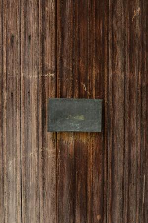 Old Wooden Door with Blank Metal Plate Stock Photo