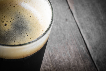 Pint of Dark Beer on Wood Background