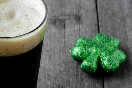Pint of Stout Beer with Green Shamrock Stock Photo