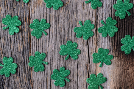 three leafed: Green Clovers or Shamrocks  on Rustic Wood Background Background for St. Patricks Day Holiday