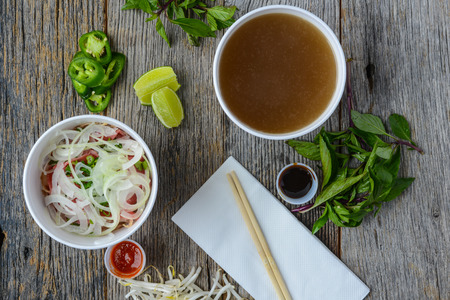 vietnamese food: Pho Fast Food To Go on Wood Background with Peppers and Basil