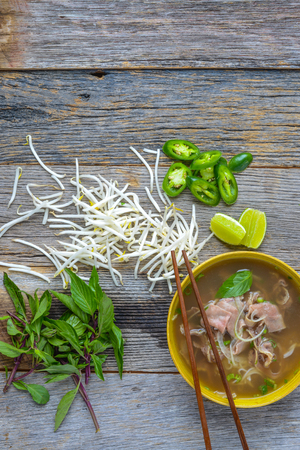 bean sprouts: Pho Vietnamese beef soup on a wooden background Stock Photo