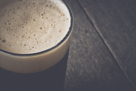 Pint of Dark Beer on Wood Background with Vintage Film Style photo
